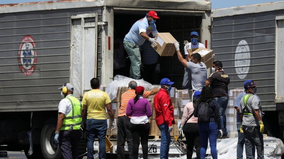 Workers load trucks with boxes of humanitarian aid from China at Caracas airport, 28 March