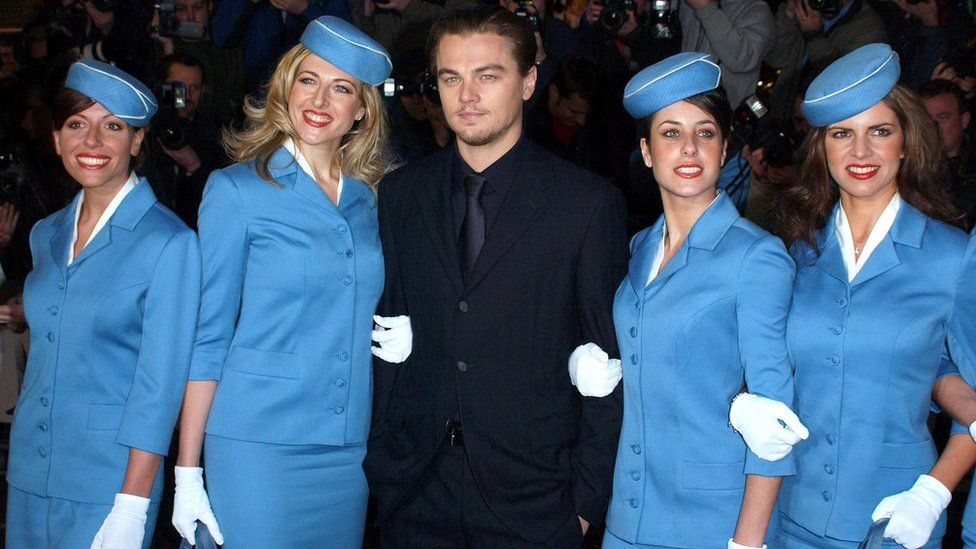 """Leonardo DiCaprio Attends The """"Catch Me If You Can"""" Uk Film Premiere in 2003, surrounded by four women dressed as flight attendants"""