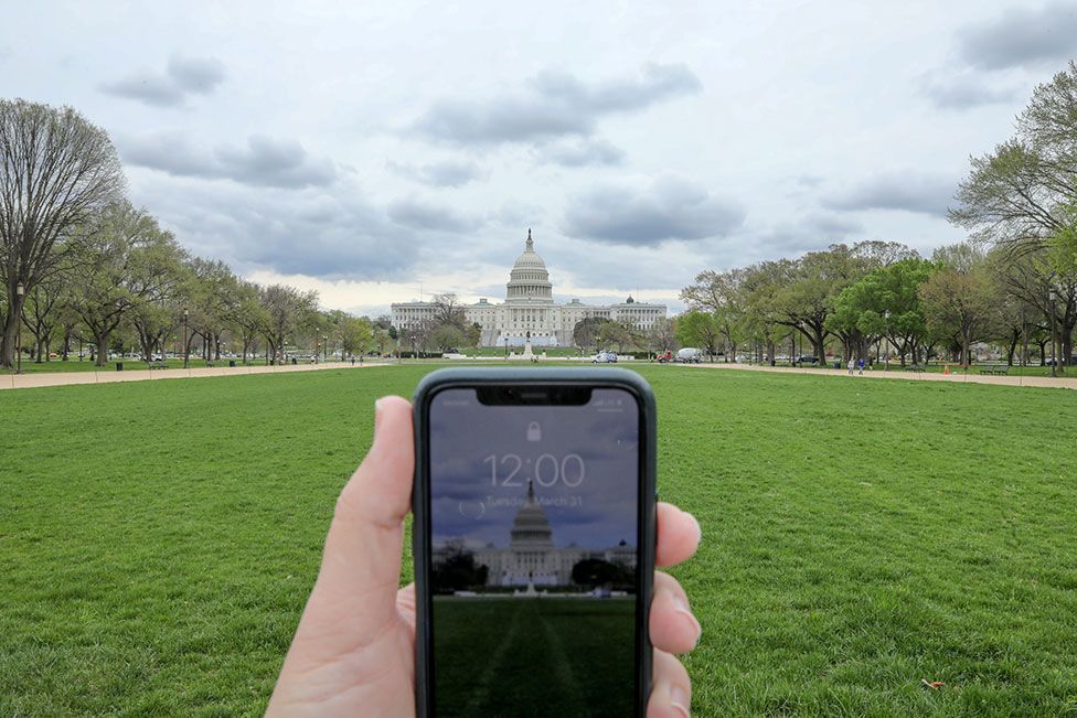 A mobile phone showing the time at noon in front of the United States Capitol, Washington, US