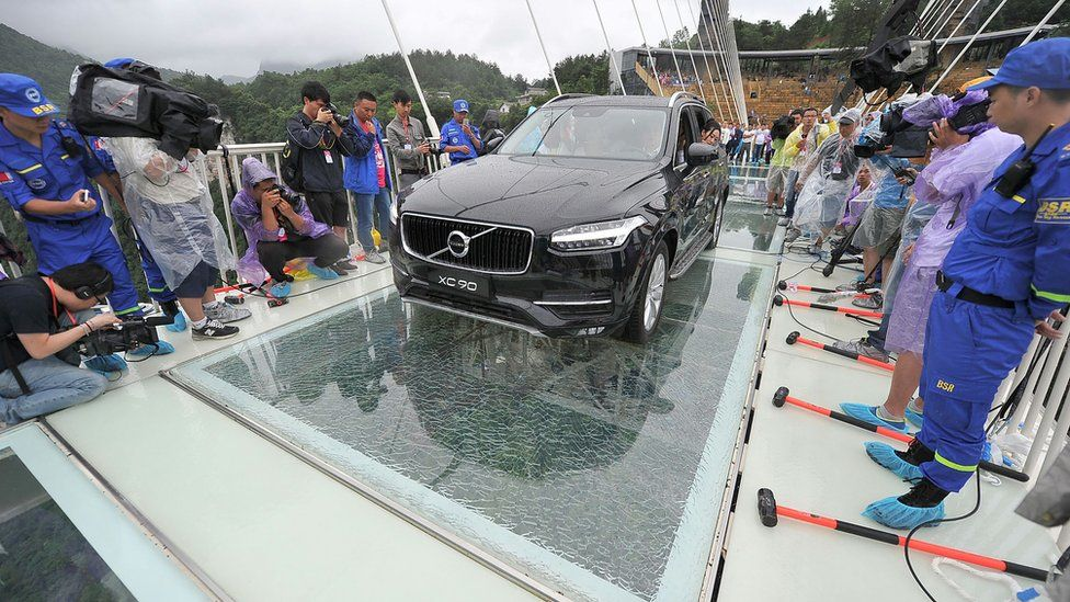 A car filled with passengers drives across the bridge