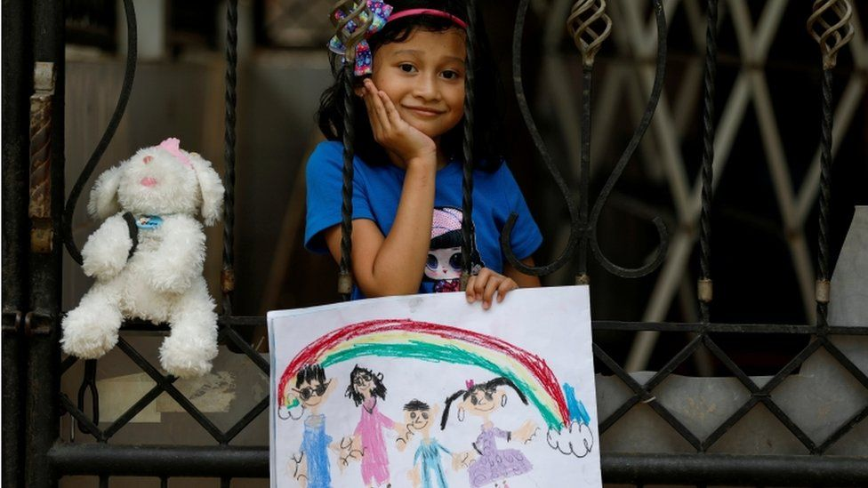 A little girl in Indonesia holds up a drawing of her family while she's stood behind a gate