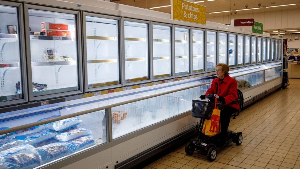 "People shop in aisles with empty shelves in a Sainsbury""s supermarket in Walthamstow, east London on March 20, 2020. - The British prime minister urged people in his daily press conference on March 19 to be reasonable in their shopping as supermarkets emptied out of crucial items - notably toilet roll - across Britain. The government said it was temporarily relaxing elements of competition law to allow supermarkets to work together to maintain supplies."