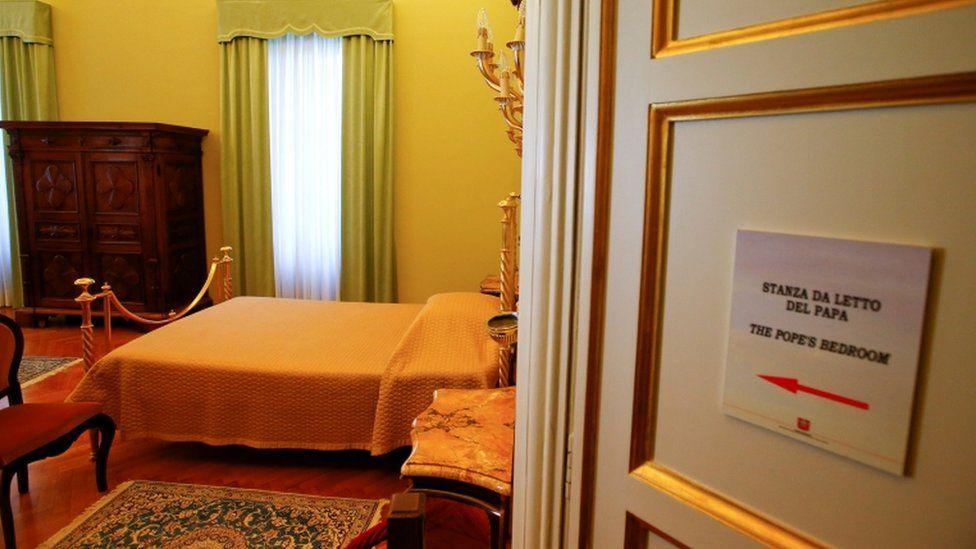 Bedroom door opens showing the Pope's bed