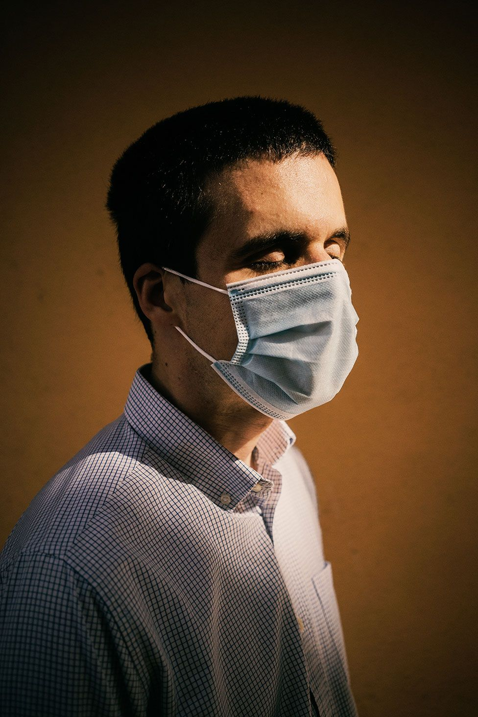 A portrait of a blind man wearing a face mask