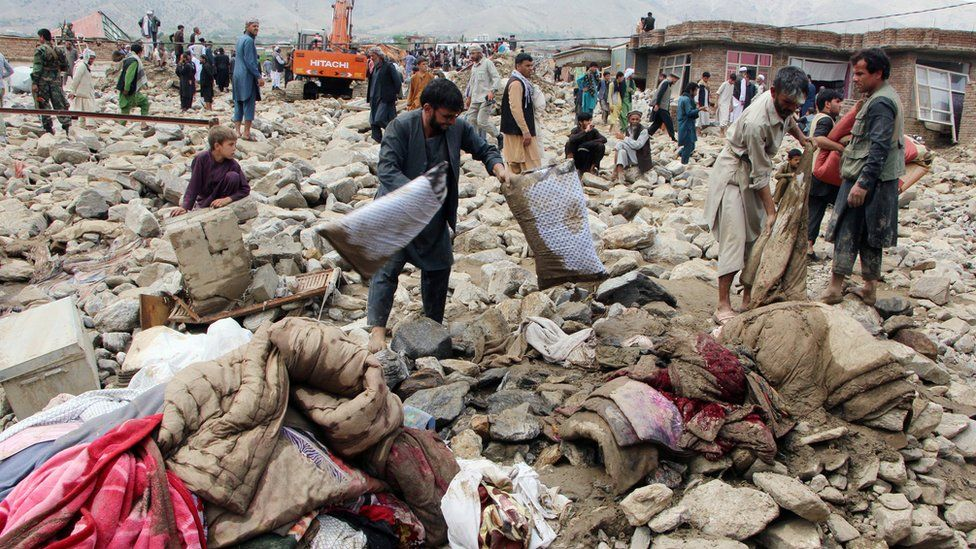 Afghan men search for their belongings after floods in Charikar