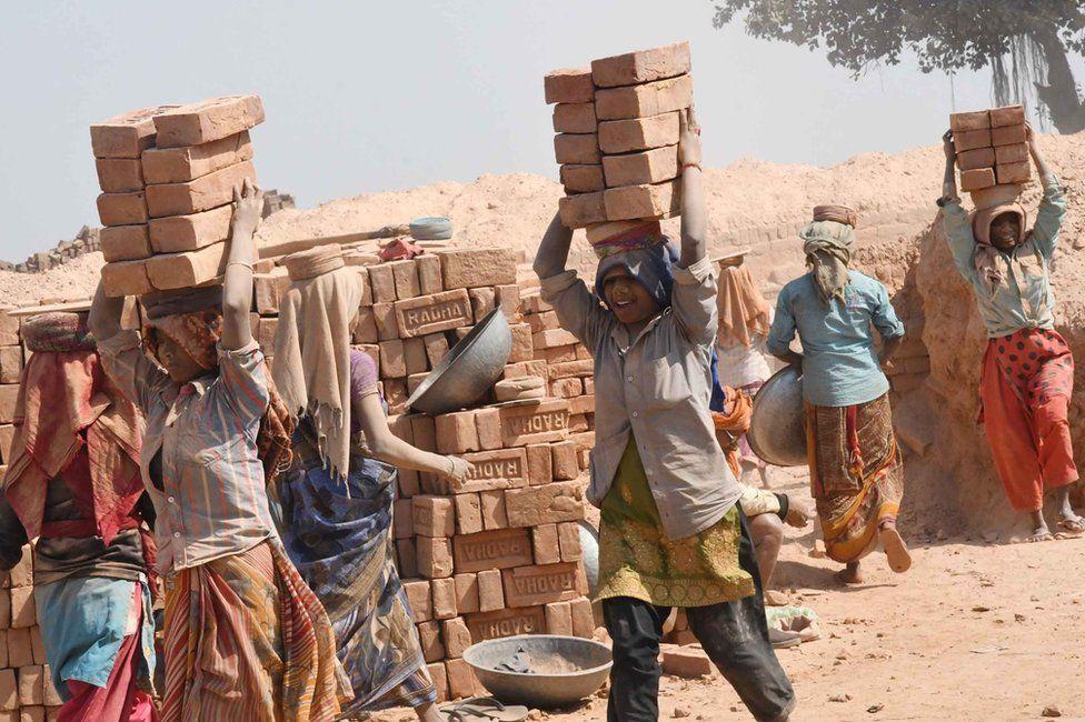 Women carry bricks at a brick kiln in Patna, India