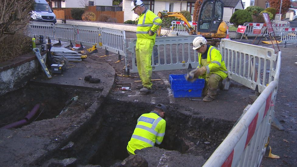 Workers trying to drain water from gas network