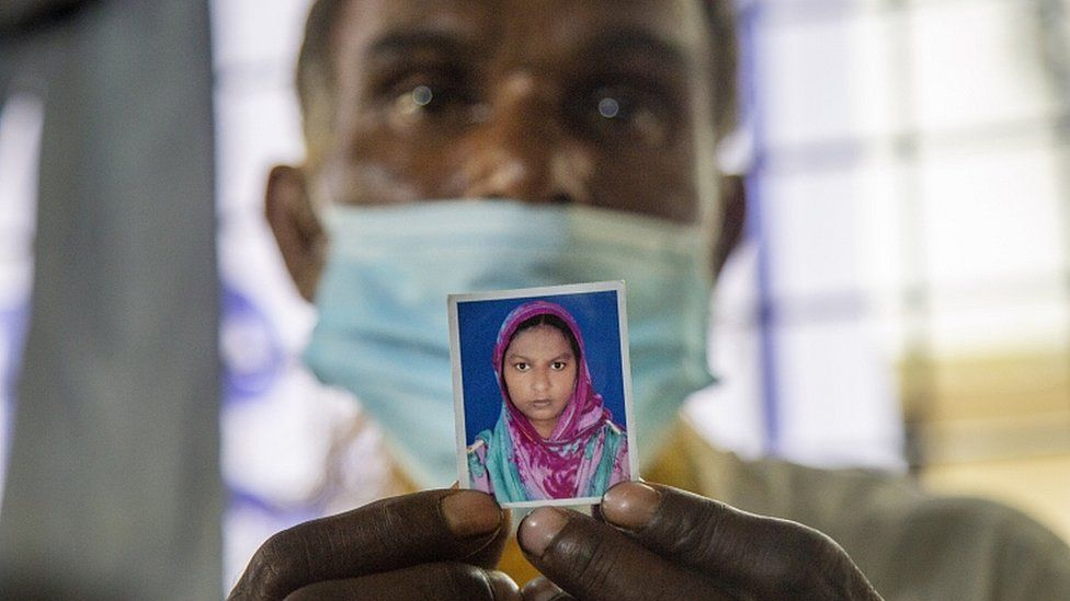 A father holds a picture of his missing daughter at the Dhaka Medical College Hospital in Dhaka, Bangladesh, 10 July 2021
