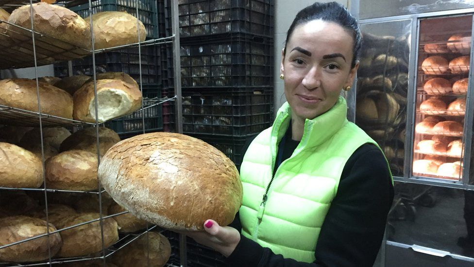 Baker owner Katalin Kollo, holding a big bread roll