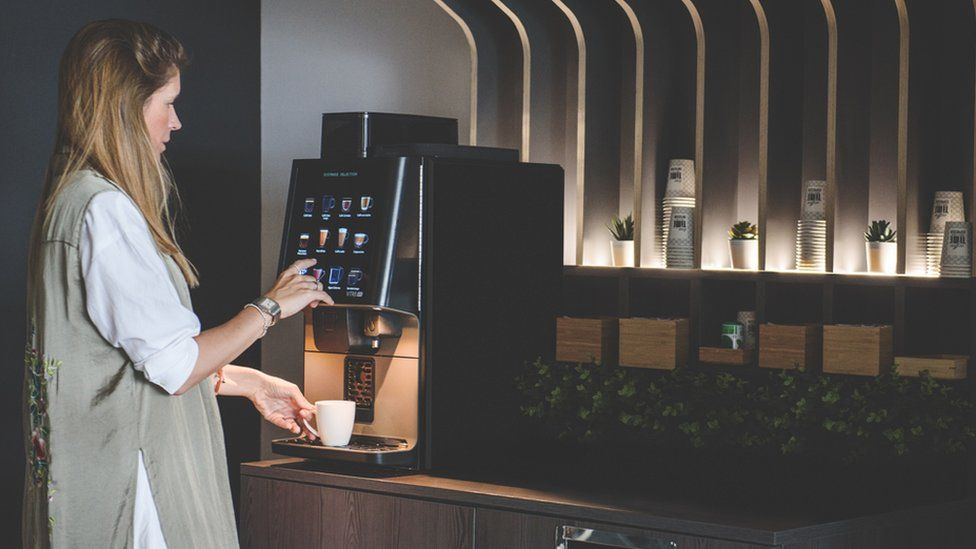 A woman using a no-touch Coffetek vending machine
