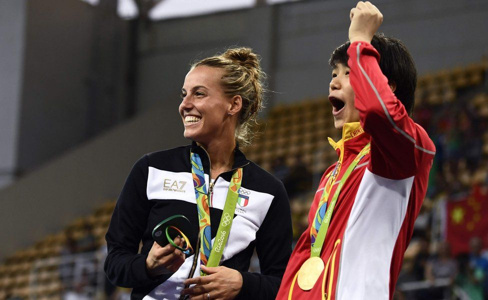 """Gold medallist China""""s Shi Tingmao (R) and bronze medallist Italy""""s Tania Cagnotto react as Silver medallist China""""s He Zi (unseen) receives a marriage proposal from Chinese diver Qin Kai during the podium ceremony"""