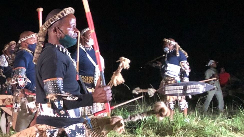 Zulu men in traditional warrior outfits at night in Nongoma, South Africa - March 2021