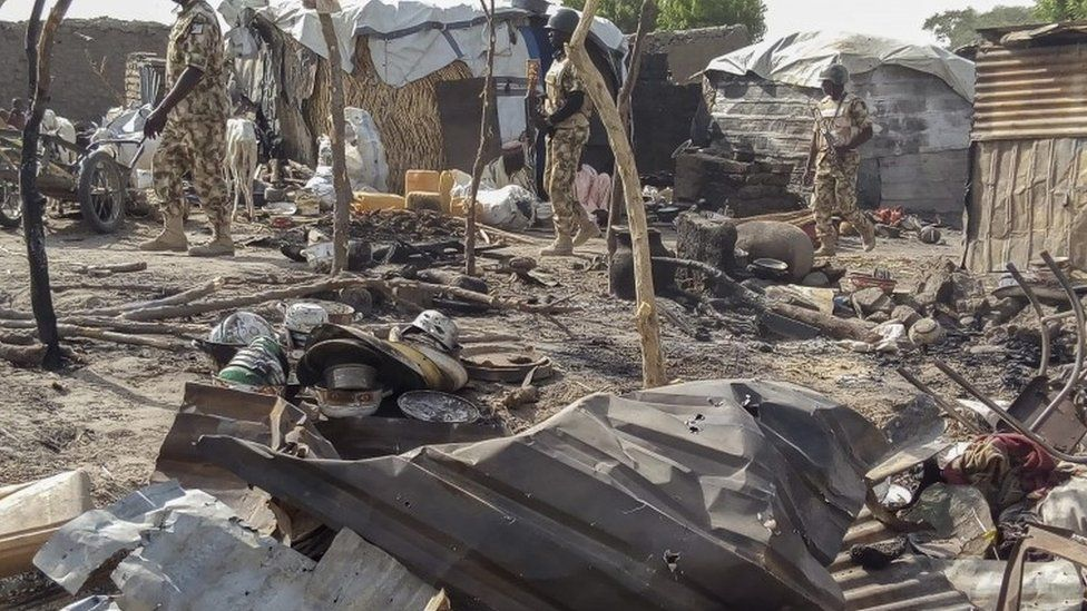 Nigerian troops during the visit of Chief of Army Staff, LT. Gen. Tukur Buratai patrol the aftermath of a bombing allegedly carried out by the Nigerian Army at a government run camp for internally displaced persons in Rann, Nigeria, 20 January 2017