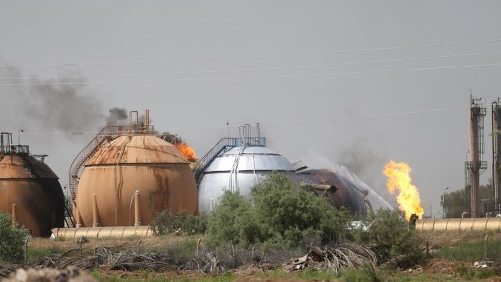 Flames and smoke rise from tanks after a suicide bomb attack on the Taji gas plant.