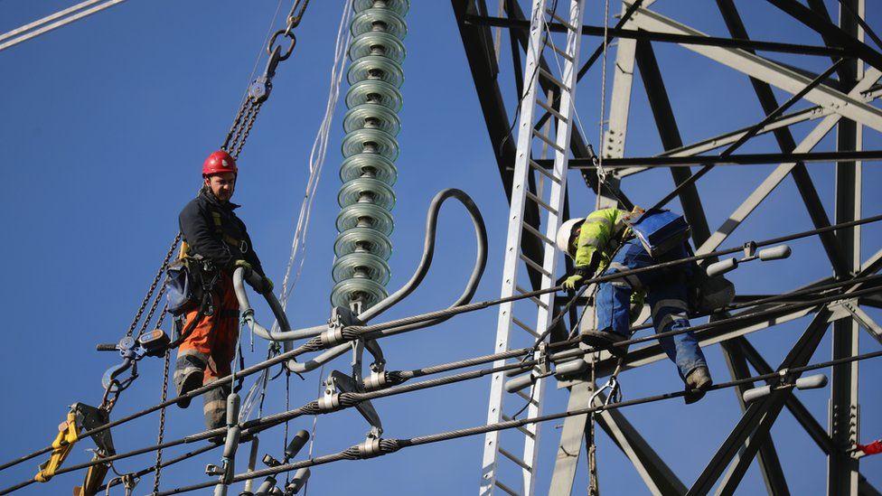workers repairing electricity pylon