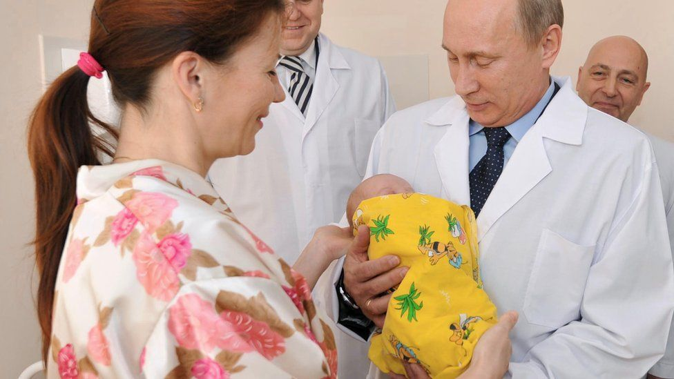Vladimir Putin holds a baby during a tour of a hospital