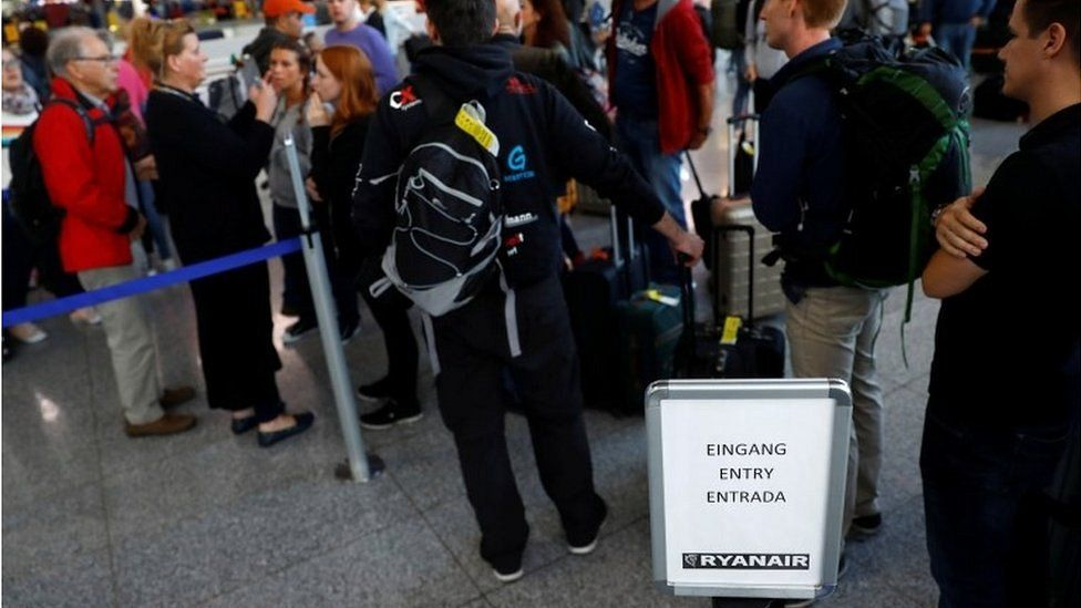 Stranded Ryanair passengers queue for hotel vouchers and new tickets