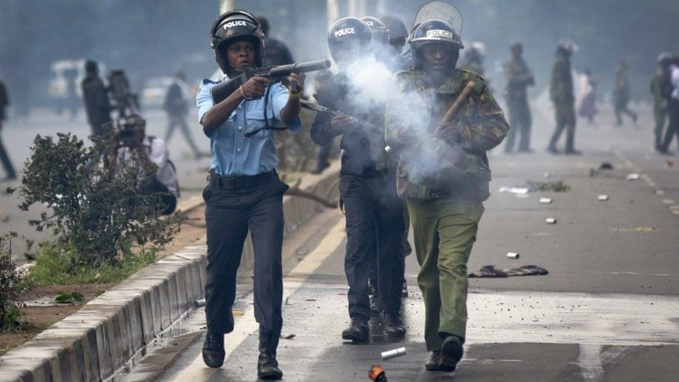 Riot police fire tear gas toward demonstrators as they flee, during a protest in downtown Nairobi, Kenya Monday, May 16, 2016