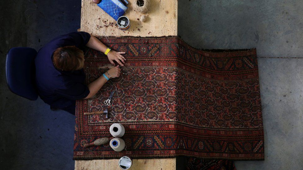 An artisan repairs a rug at the Royal Tapestry Factory in Madrid, Spain, October 7, 2016