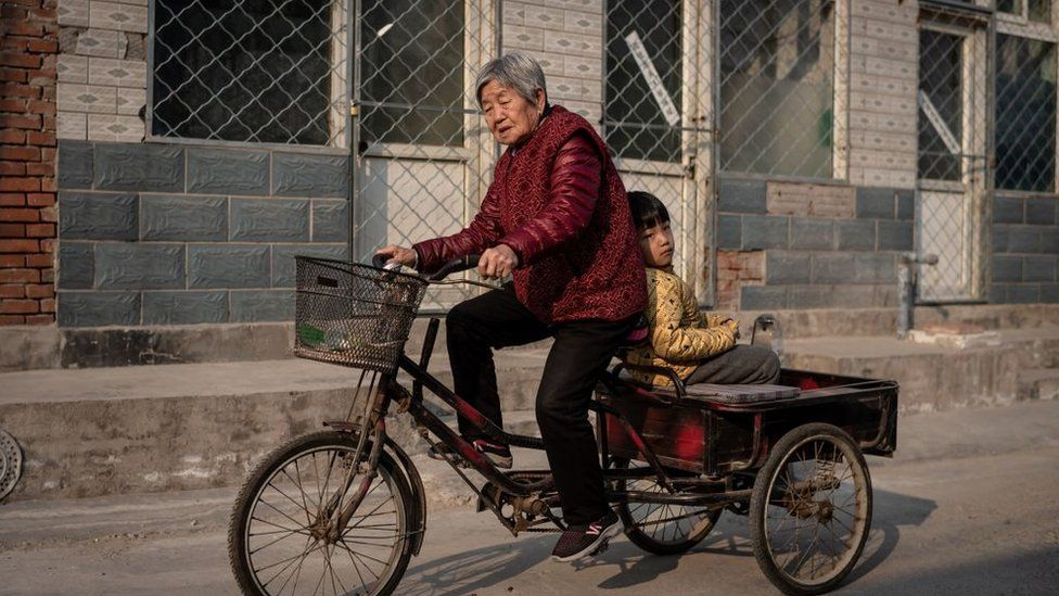 An elderly woman drives a tricycle as a boy sits on a back seat on a street in Beijing.