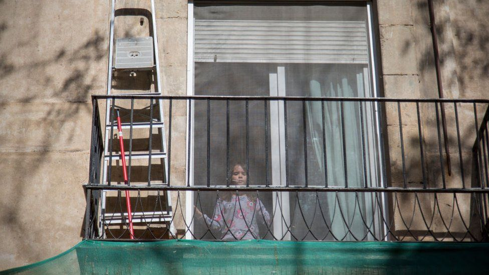 A girl in confinement looks out the window in Barcelona in April