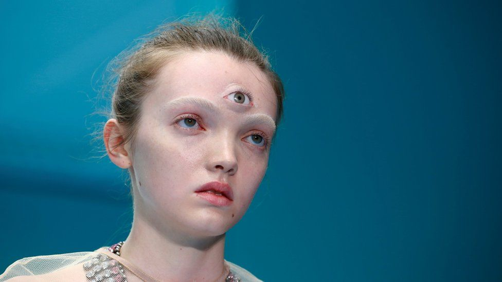 Female model with a prosthetic third eye attached to her forehead