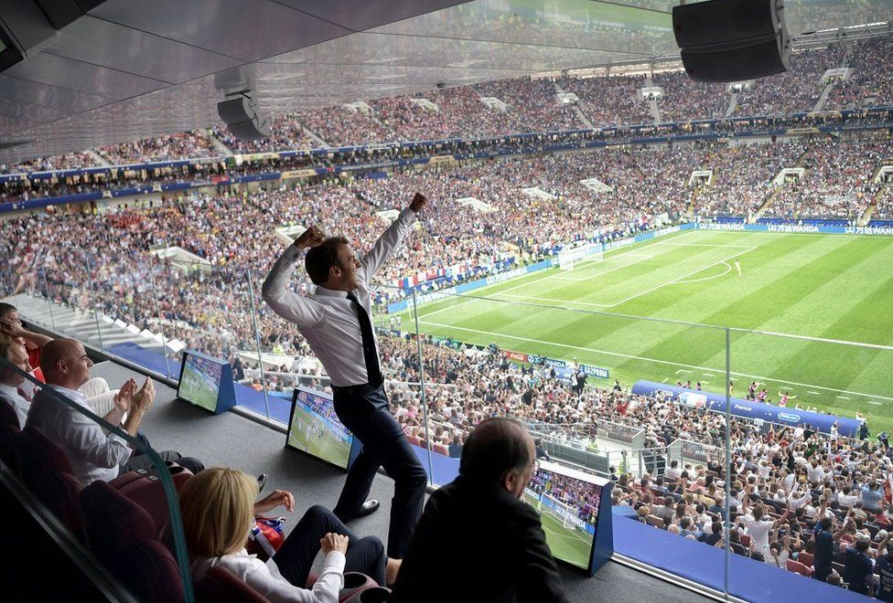 Emmanuel Macron raises his arms as he watches the World Cup final in a stadium