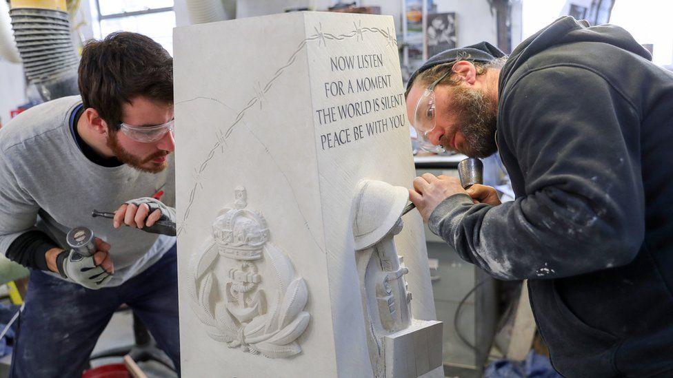 Prisoners carving a war memorial