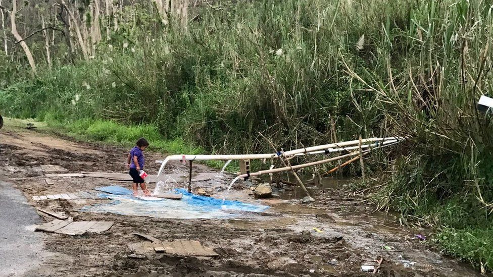 A child gathers water from a pipe in rural Puerto Rico