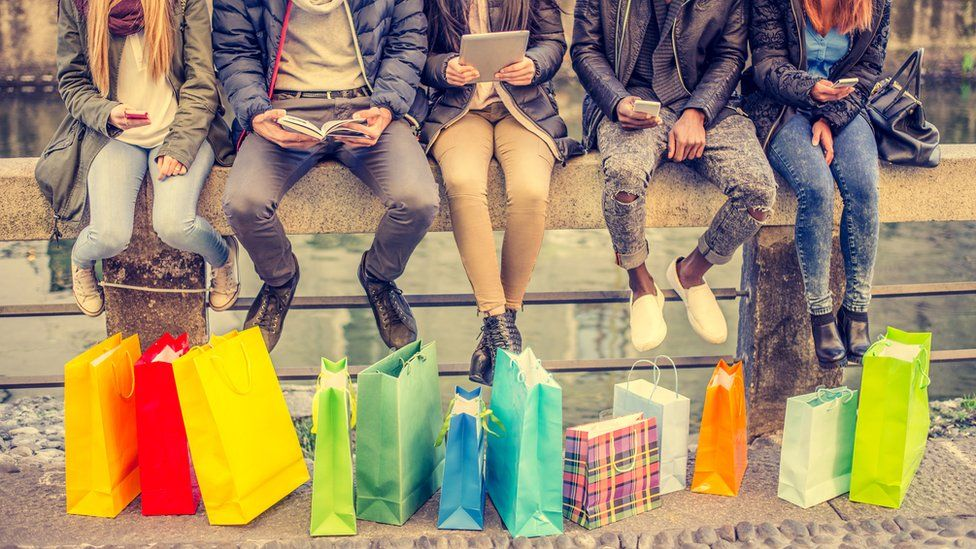 Friends with shopping bags and electronic gadgets