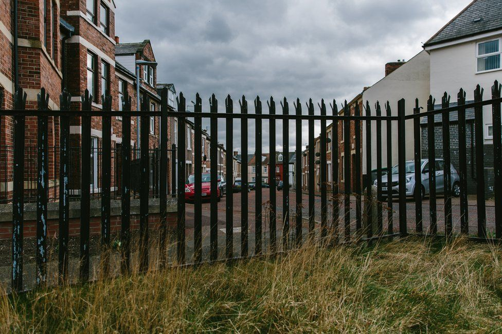 The corner of the allotment showing a metal fence on to a residential area