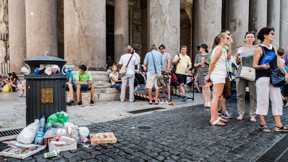 Tourists stand next to a bin overflowing with waste in front of the Ancient Pantheon, in central Rome on July 27, 2015
