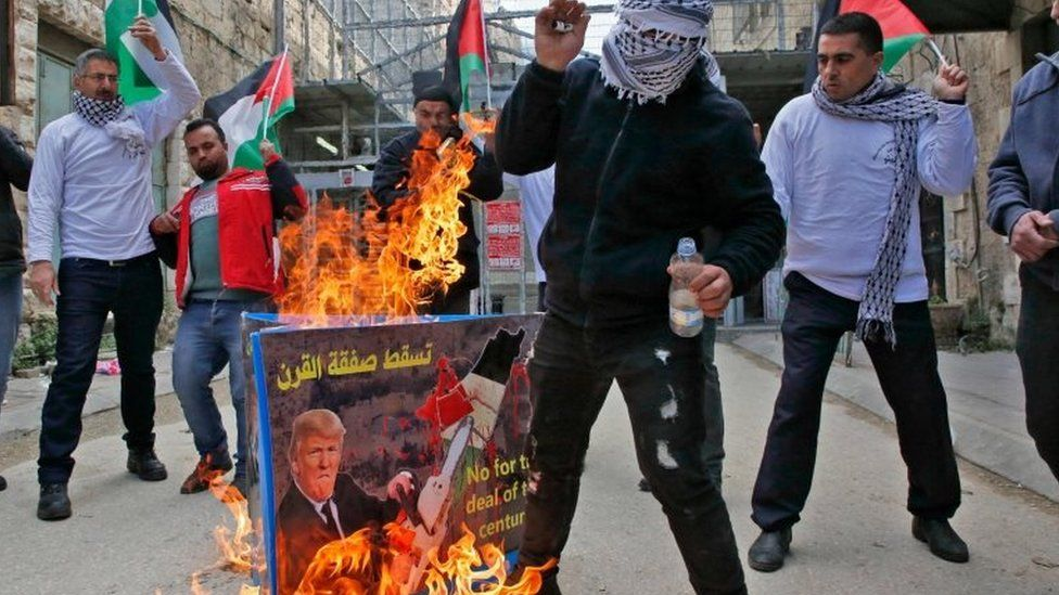 Palestinian protestors set ablaze a poster with a picture of US President Donald Trump during a demonstration in Hebron in the Israeli occupied West Bank on 22 February 2019