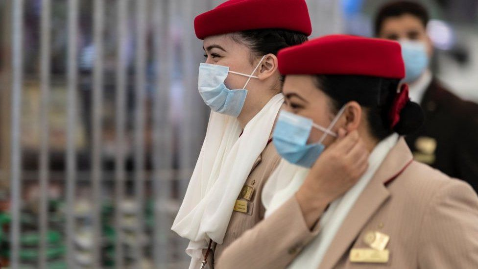 Crew members from Emirates airline are seen leaving Hong Kong international airport.