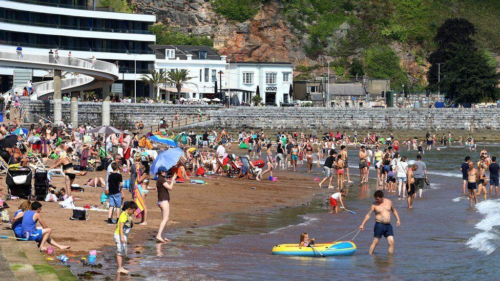 People on the beach in Torquay, in Devon