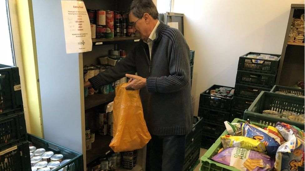 A volunteer filling a bag with food