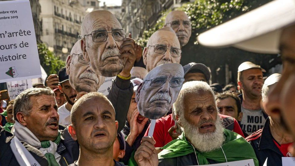 Protesters holding masks showing the face of Lakhdar Bouregaa