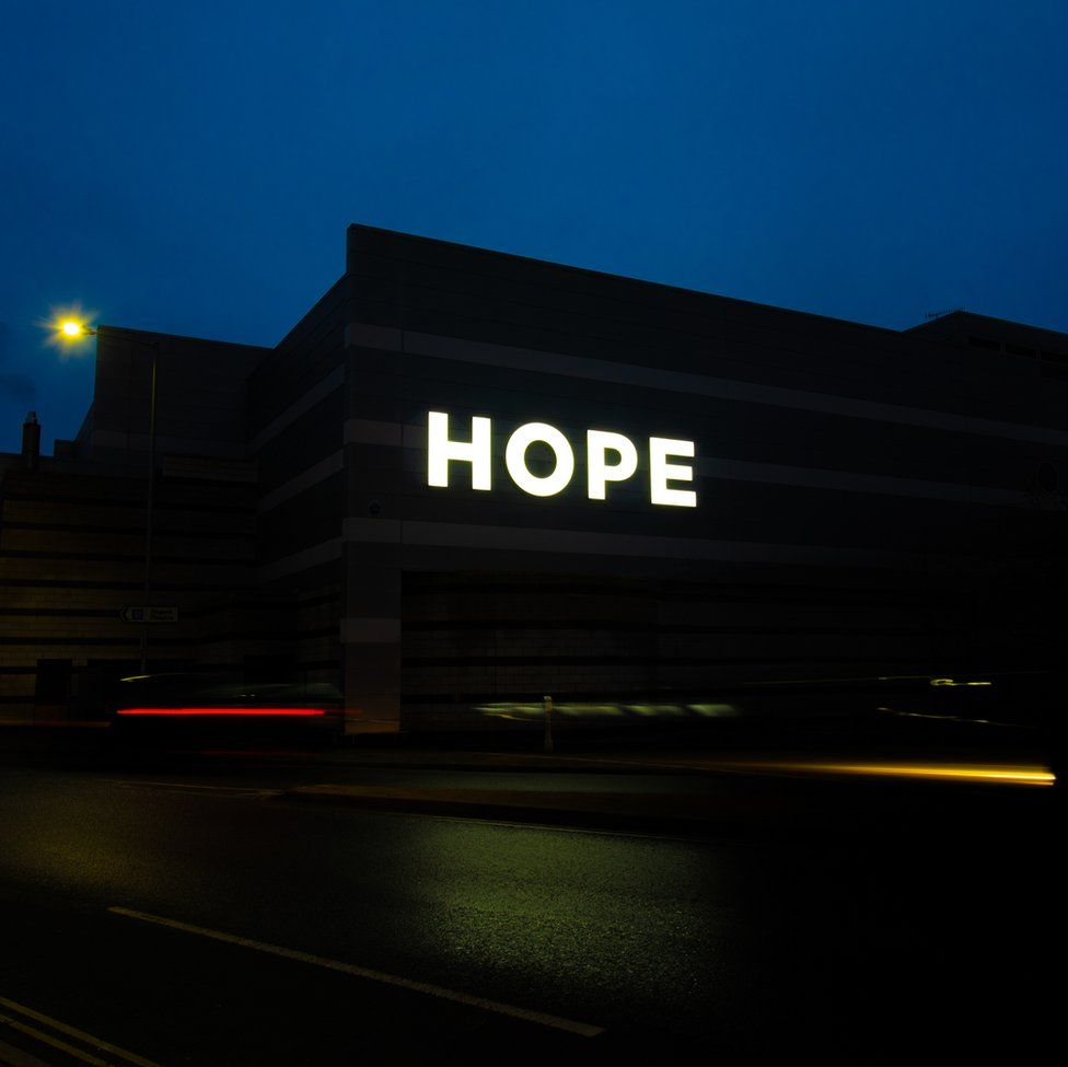 An image of a dark sky and a large sign that says Hope