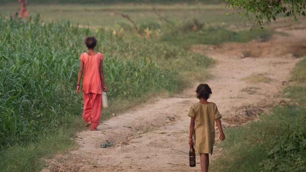 Children walk through the fields in Badaun district of Uttar Pradesh in India