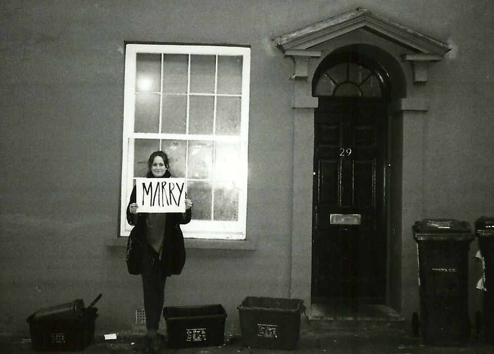 Molly with a sign reading marry
