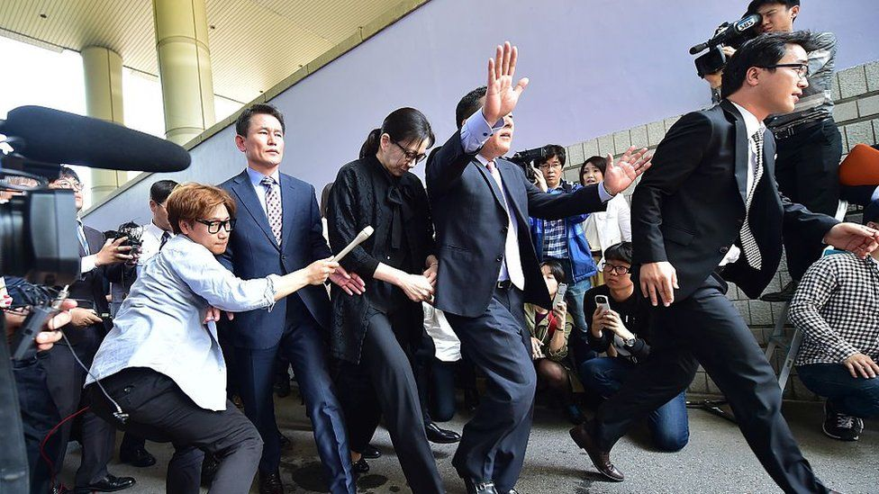 Former Korean Air (KAL) executive Cho Hyun-Ah (C) leaves after she received a suspended jail sentence and was freed by a Seoul appeals court in Seoul on May 22, 2015, after she had been jailed for a year in February for disrupting a flight in a rage over macadamia nuts.