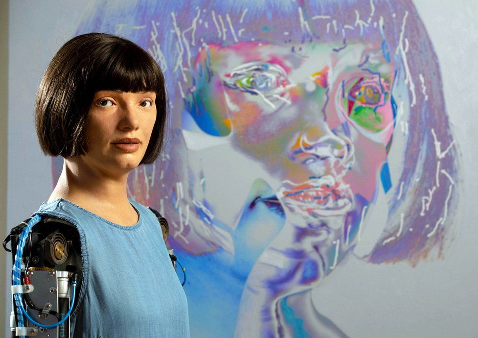 Ai-Da the robot poses next to one of her self-portraits at The Design Museum in London