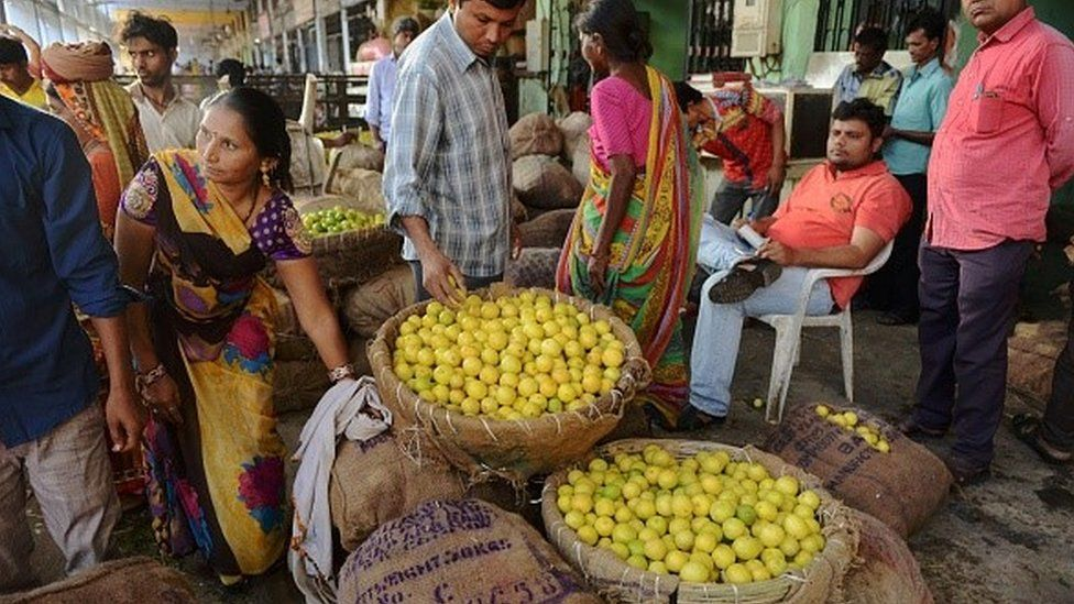 Indian customers check the quality of lemons for sale at a market in Ahmedabad