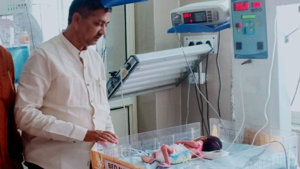 Local politician Rajesh Kumar Mishra with the baby in hospital