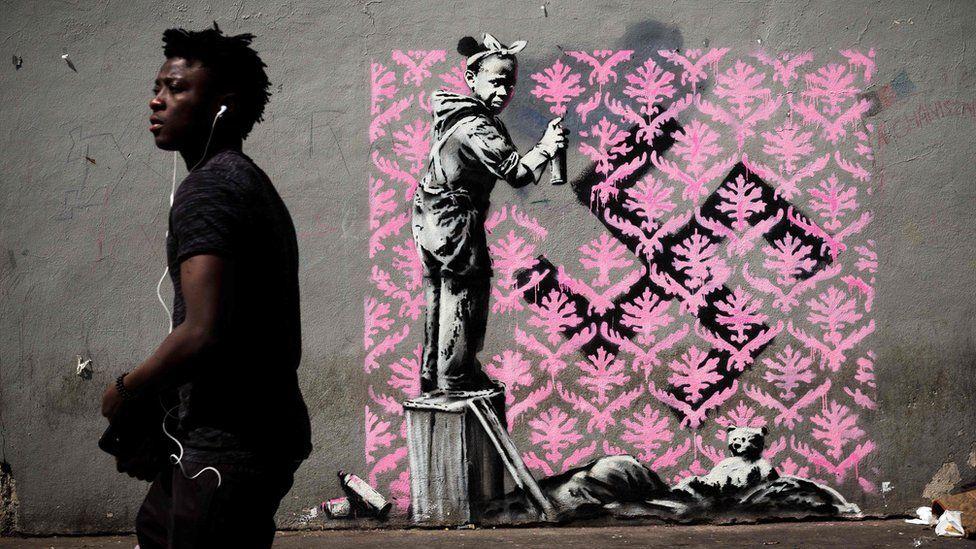 A man walks past a recent artwork by street artist Banksy in Paris