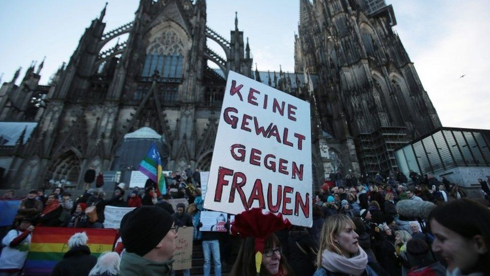 """A demonstrator holds a sign in German that reads """"No violence against women"""" during a demonstration in the wake of the sexual assaults on New Year's Eve, outside the cathedeal in Cologne, Germany, 09 January 2016"""