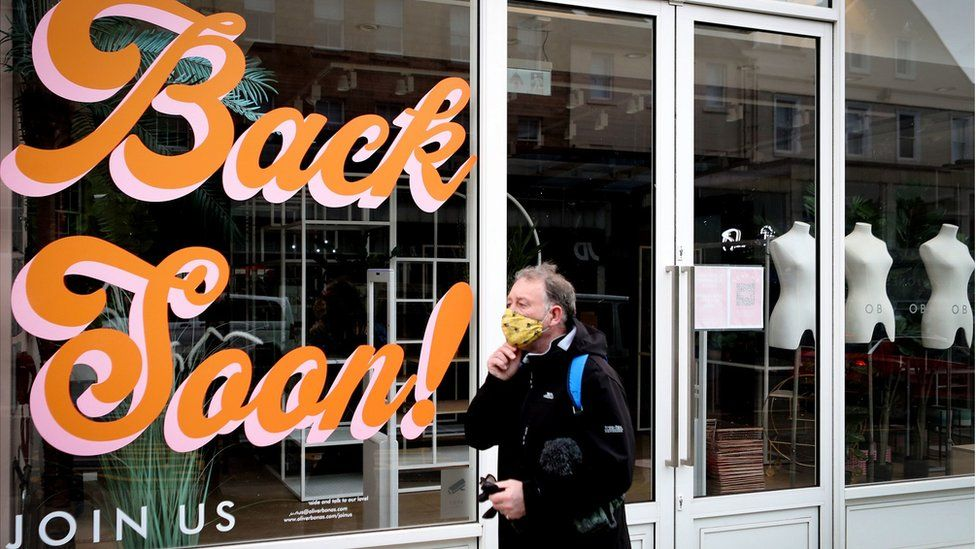 "A man walks past a sign reading ""Back Soon"" in the window of a closed shop in Edinburgh city centre"