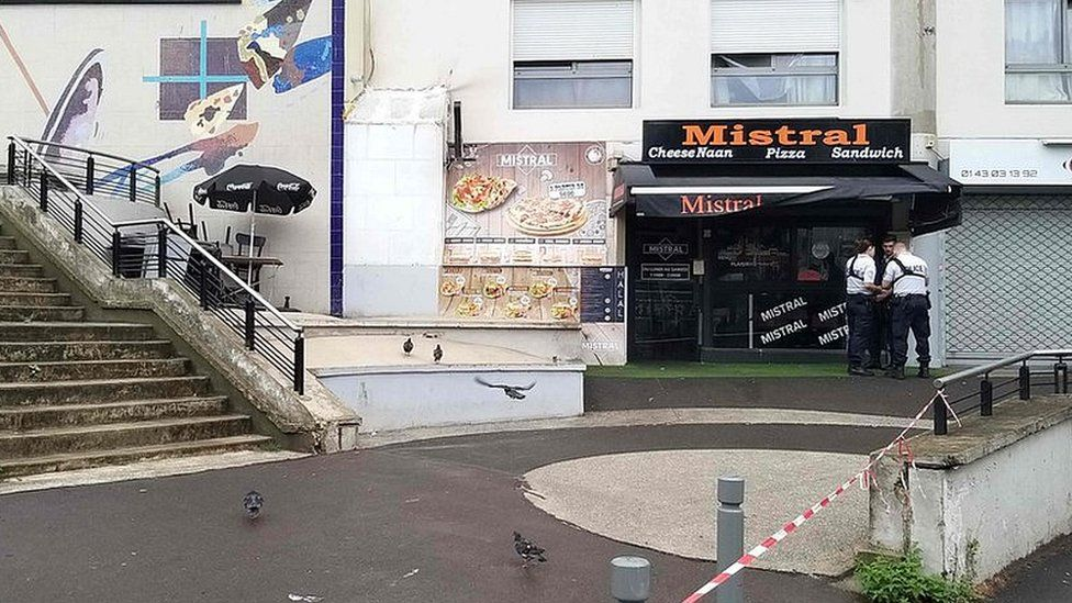 Police stand in front of the shop where a waiter was shot dead by a customer allegedly angry at having to wait for a sandwich, in the eastern Paris suburb of Noisy-le-Grand on August 17, 2019