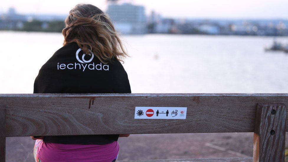 Woman sat at park bench in Cardiff with warning sign on back