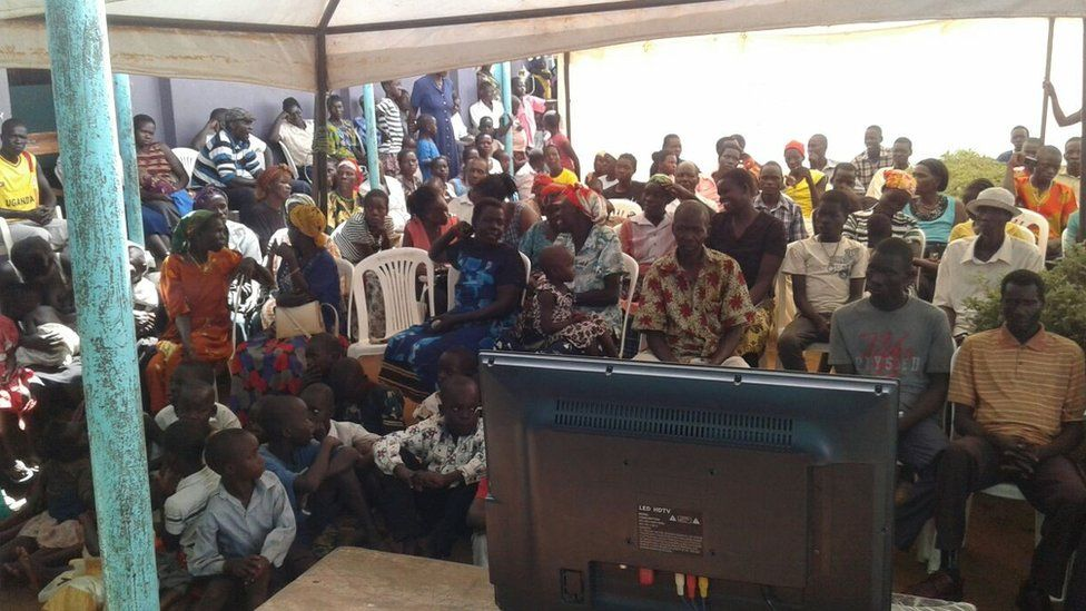 Villagers in Lukodi, scene of one of the attacks Mr Ongwen is accused of, watch his trial